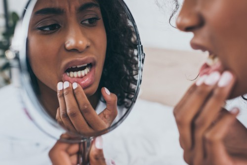 woman with tooth pain examines her teeth in mirror